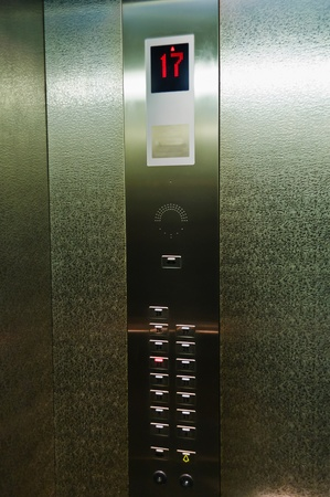 Button and indicator in the elevator. Lift with steel walls