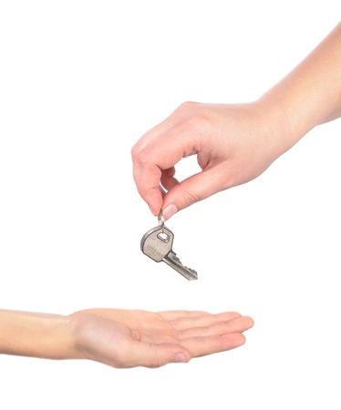 photo handing over a key female hand holding a key and handing it over to another woman concep picture photo