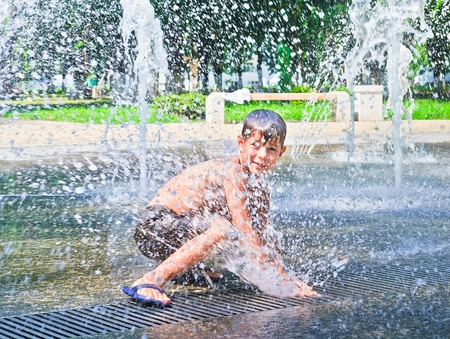 The boy is bathed in the fountain. Summer hot weather Standard-Bild