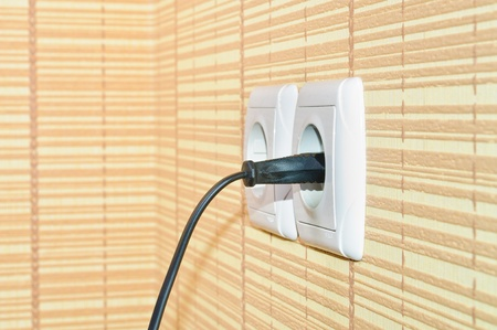 Power plug into the socket on the wall photo