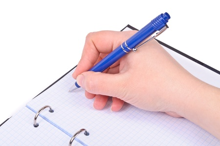A hand with a ballpoint pen writes in a notebook  Stock Photo - 12682851