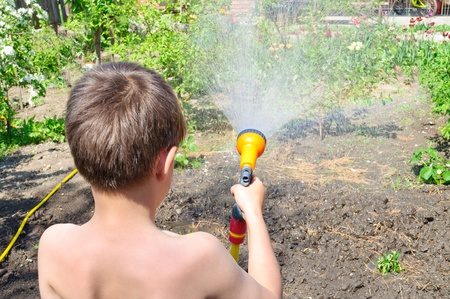 Boy watering plants in the garden with a hose with a sprayer Stock Photo - 13431162