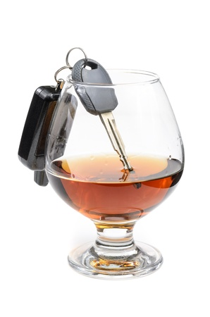 drink and drive: glass of alcohol and car keys. Photo isolated on white background