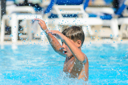 Boy splashes water in the pool. Stock Photo