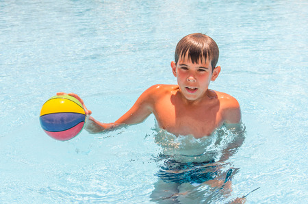 Boy with a ball in the pool. Photo for microstock