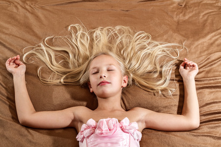 little blonde girl: Beautiful little girl sleeping on bed  Girl is wearing pink dress  Top view Stock Photo