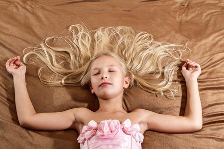 vestido de noche: Niña hermosa durmiendo en la cama Chica lleva vestido rosa Vista superior