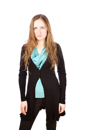 suspiciously: Displeased young woman with tired look. Girl is wearing green shirt, black cardigan and skinny pants.. Isolated on white background Stock Photo