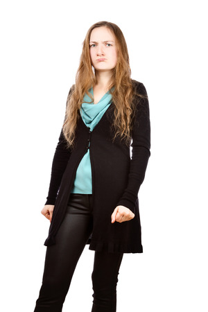 Angry young woman with clenched hands into fists. Girl is wearing green shirt, black cardigan and skinny pants. Isolated on white background photo