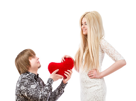 Romantic man on his knees holding a red heart and an excited blonde woman photo
