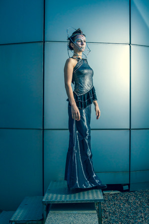 Beautiful woman in a silver dress with crystals on her face photo