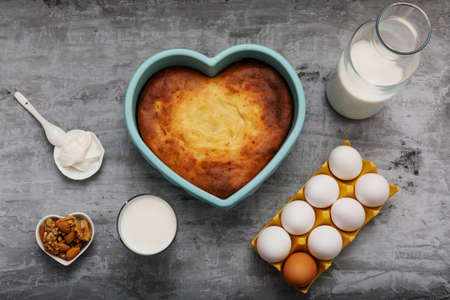 Heart-shaped casserole and ingredients on concrete.