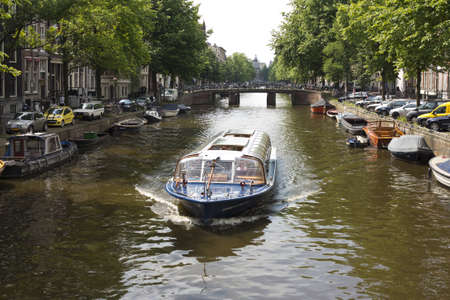 Boat with tourists strolling along the canals of Amsterdam