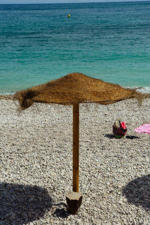 Brown yellow umbrella on a beautiful mediterranean beach