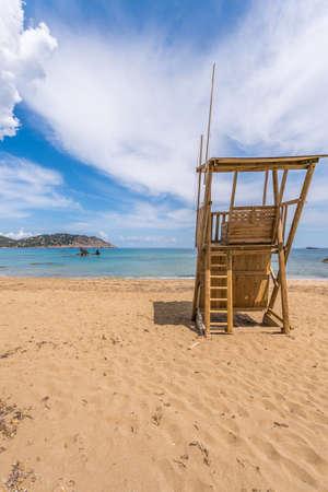 Lifeguard tower sandy beach white clouds sea blue sky, Figueral beach, Ibiza