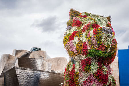 BILBAO, SPAIN - OCTOBER 1  Guggenheim Museum and Puppy sculpture on October 1, 2013 in Bilbao, Spain  The museum was designed by Frank Ghery and the Puppy sculpture by Jeff Koons Editorial