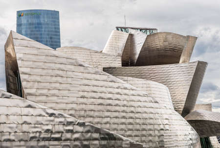 BILBAO, SPAIN - OCTOBER 1  Exterior of The Guggenheim Museum and Iberdrola Tower on October 1, 2013 in Bilbao, Spain  The Guggenheim is a museum of modern and contemporary art designed by Canadian-American architect Frank Gehry on October 1, 2013 in Bilba Editorial