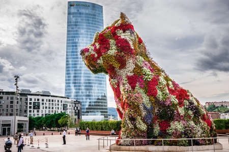 BILBAO, SPAIN - OCTOBER 1  Iberdrola Tower and Puppy sculpture on October 1, 2013 in Bilbao, Spain  The tower was designed by architect Caesar Pelli and the Puppy sculpture by Jeff Koons