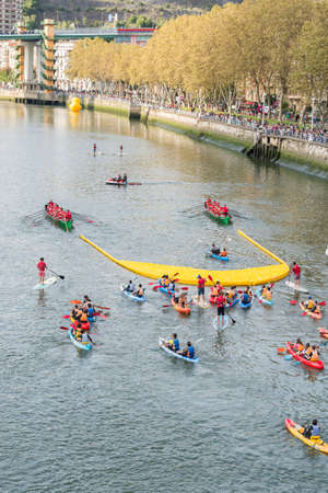 BILBAO, SPAIN - OCTOBER 13   Two ships carrying plastic ducks to the finish line during the competition organized by the foundation Walk on Project  WOPATO  on October 13, 2013 in Bilbao, Spain