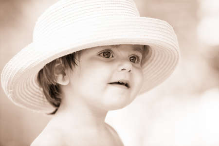 Little girl with hat setting smiles at the camera