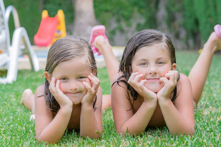 little girls lying in garden and setting smiles at the camera photo