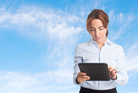 Business woman over clouds background. Reading from a tablet Stock Photo