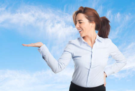 Business woman over clouds background. Showing a product