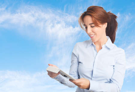 Business woman over clouds background. Using a tablet
