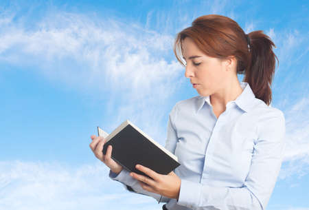 Business woman over clouds background. Reading a black book