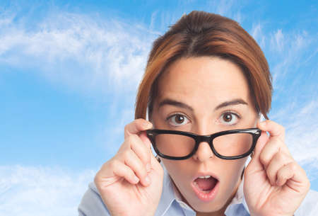 bifocals: Business woman over clouds background. Looking surprised Stock Photo