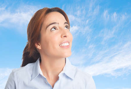 Business woman over clouds background. Looking happy Stock Photo