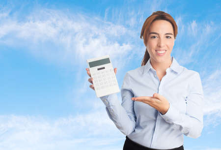 Business woman over clouds background. Showing a calculator