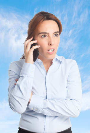 gloominess: Business woman over clouds background. Upset using a smartphone