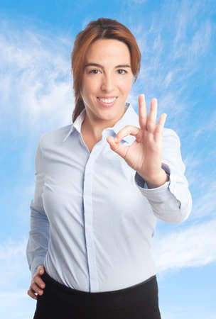 Business woman over clouds background. Doing the ok gesture Stock Photo
