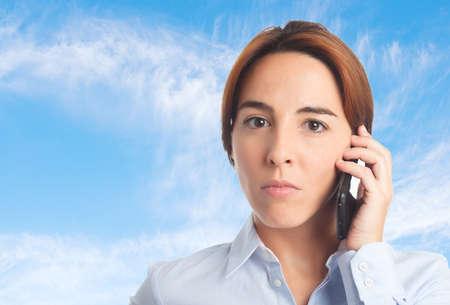 desolaci�n: Mujer de negocios sobre fondo de las nubes. Buscando seria usando un tel�fono inteligente
