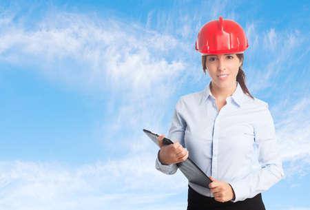 casco rojo: Mujer de negocios sobre fondo de las nubes. El uso de un casco rojo y la celebraci�n de una carpeta negro