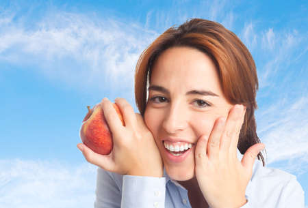 Business woman over clouds background. Looking funny with a red apple