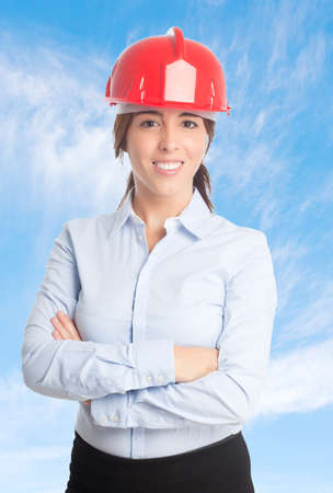 Business woman over clouds background. Looking happy with a red helmet Stock Photo