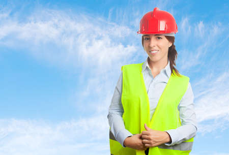 Architect woman over clouds background. Wearing red helmet Stock Photo