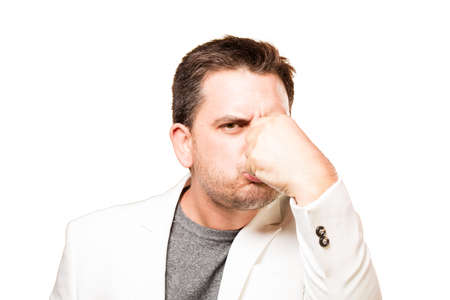 bad smell: Man wearing a white jacket. Doing bad smell gesture. Stock Photo