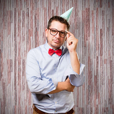 reflexion: Man wearing a red bow tie and party hat. In a deep reflexion. Foto de archivo