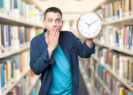 Young man wearing a blue outfit. Holding a clock. Looking surprised. Stock Photo