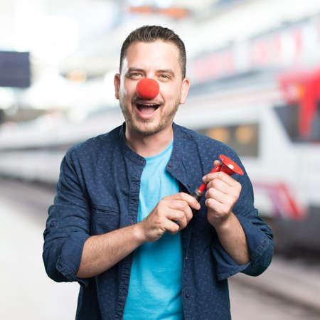 clown nose: Young man wearing a blue outfit. Wearing a clown nose. Playing with red horn. Stock Photo