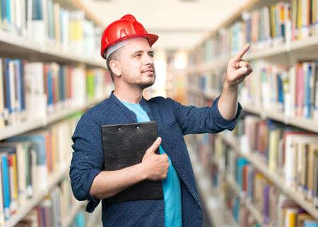 casco rojo: El hombre joven que llevaba un traje azul. El uso de casco rojo. El señalar algo.