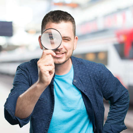 Young man wearing a blue outfit. Using a magnifying glass. Smiling.