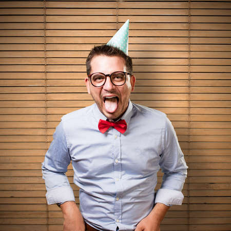loony: Man wearing a red bow tie and party hat. Pulling his tongue out.