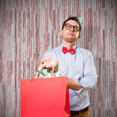 unhappy man: Man wearing a red bow tie and party hat. Holding gift. Looking tired.
