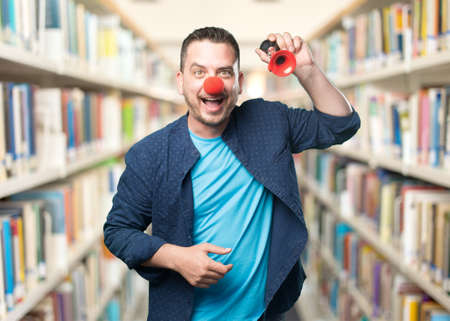 buffoon: Young man wearing a blue outfit. Wearing a clown nose. Playing with red horn. Stock Photo
