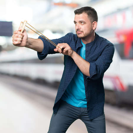 Young man wearing a blue outfit. Using a slingshot. pointong to the side. Stock Photo