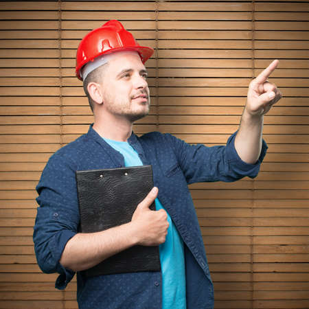 casco rojo: Young man wearing a blue outfit. Wearing red helmet. Pointing to something.